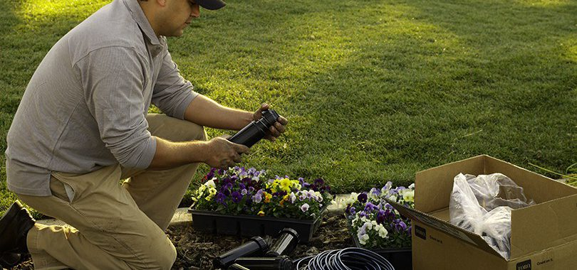 Man assembling irrigation system with opened box next to him in backyard